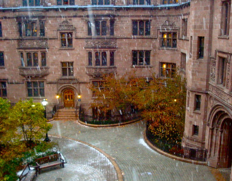 Snow falling and melting on the cobblestones in a courtyard.