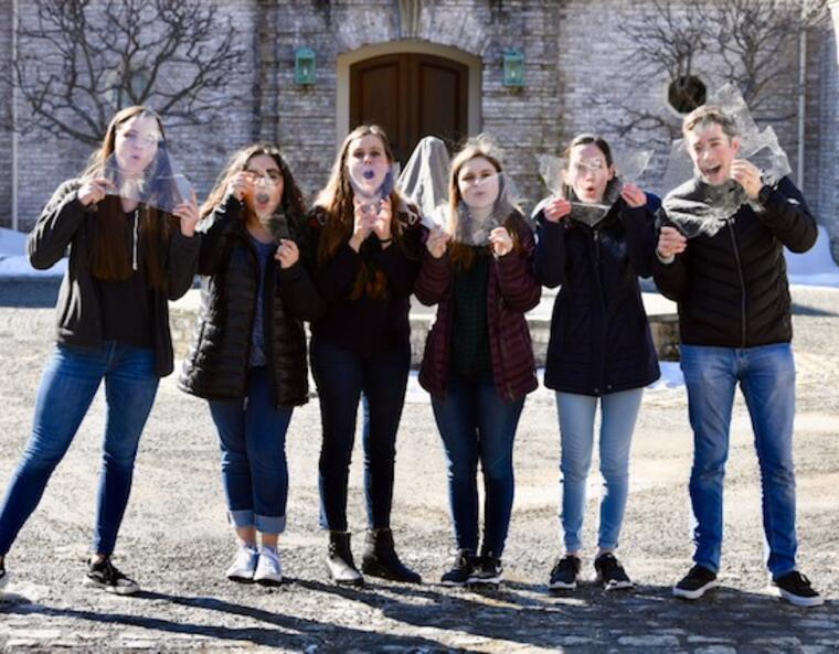 5 people pose with pieces of ice in front of their face
