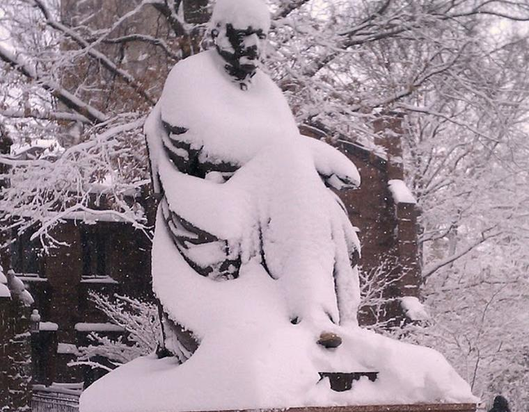 A statue on campus, unrecognizable beneath a thick covering of snow.