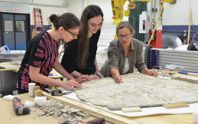 Students and a professor work on restoring a piece of art
