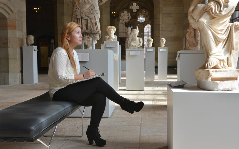 A student sketches a sculpture in the Yale Art Gallery