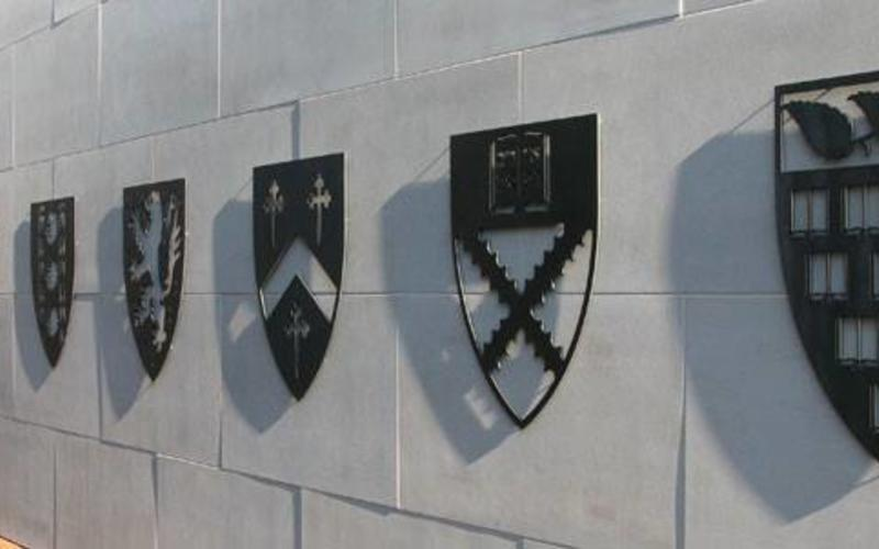 A wall adorned with several Residential College shields.
