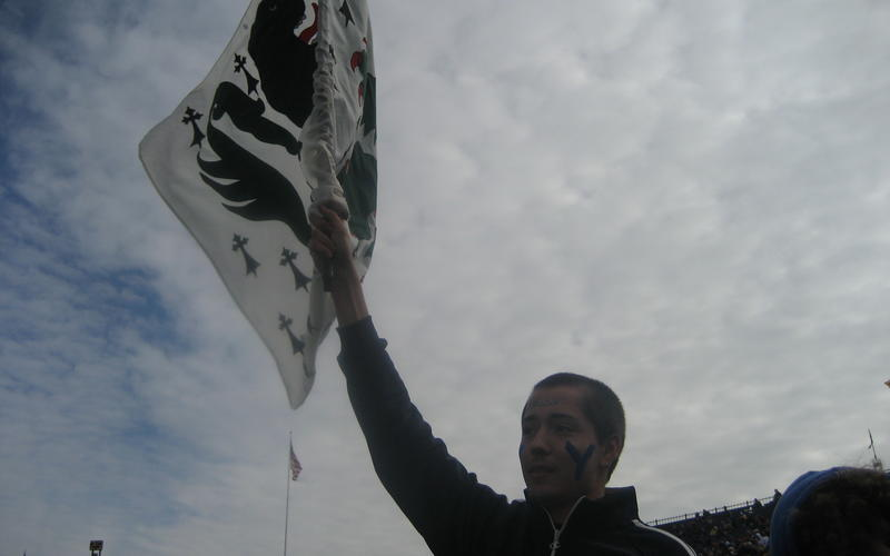 A student waving a Jonathan Edwards College flag at an outdoor event.