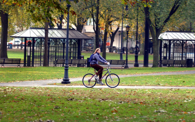 A student riding her bike across the New Haven Green.
