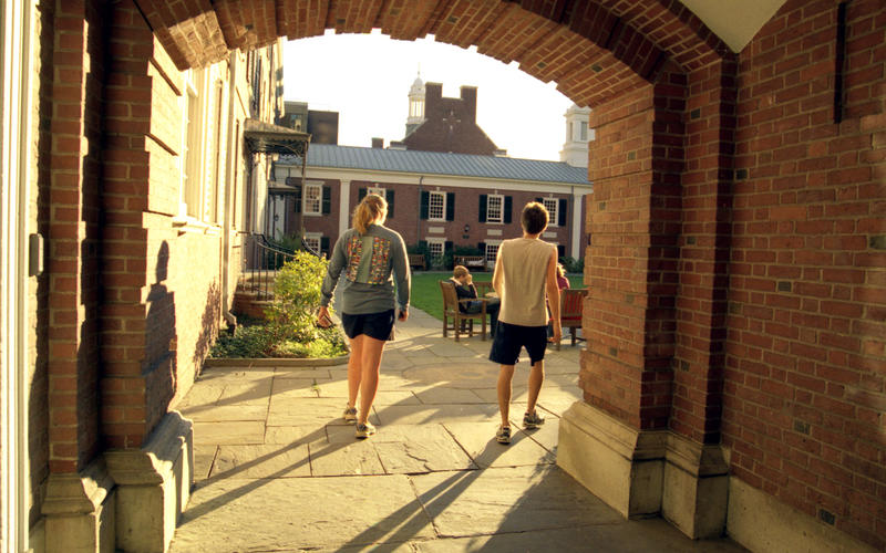 Students pass under a brick archway into the sunlit Pierson College courtyard.