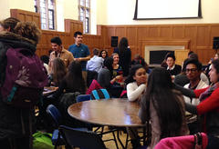 A diverse group of students in conversation with each-other, seated together at small tables.