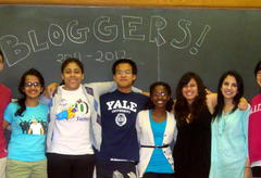 "A diverse group of students standing in front of a blackboard reading ""Bloggers! 2011-2012""."