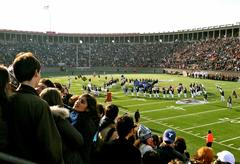 The marching band performing to a packed stadium on the Yale Bowl football field.