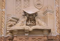 A carving of a scholar in robes and mortarboard, sleeping with his head propped up above an enormous book.
