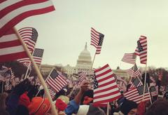 A dense crowd of people waving small American Flags in front of the United States Capital Building.