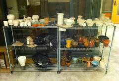 Ceramic cups, pots and vases on a drying rack.