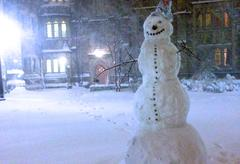 A tall snowman standing outside a residential college.