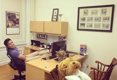 Photo of John Yi at his desk in the admissions office