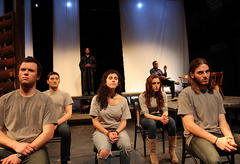 """Grim-faced actors on stage in a production of """"The Laramie Project"""""""