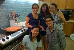 A group of students pose with a freshly-cooked dinner in a residential college kitchen.