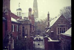 Rooftops and walkways dusted with snow near a campus gate.
