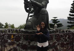 The author mimicking the pose of a Chinese statue behind her.