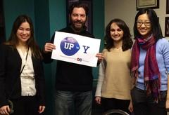 Lou Mangini with three female students, smiling and holding up their campaign sign.